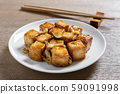 stir fried fish tofu with oyster sauce in a ceramic dish on wooden table, close up. 59091998