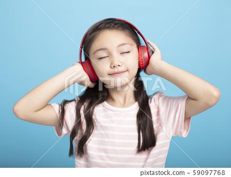 happy little girl with headphones listening to 59097768