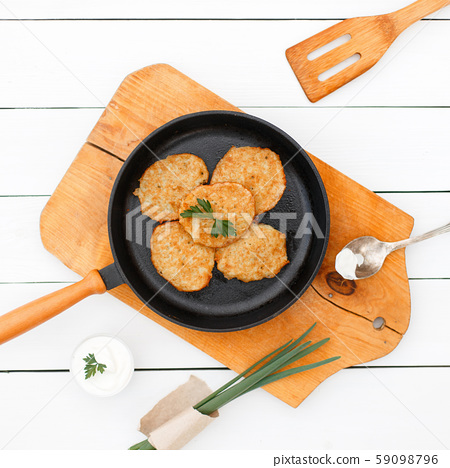 Potato pancakes on a cast-iron frying pan  59098796