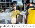 Courier delivering groceries to a young woman outdoors 59115517