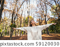 Cheerful woman loving autumn nature in the park 59120030