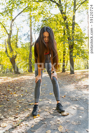 Beautiful woman making a break during her run 59120724
