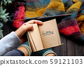 woman feet with socks, sitting at balcony, hand hold notebook, knitting colorful scarf 59121103