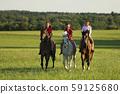 Teenage girls on horse walking on meadow in 59125680