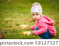 Portrait of adorable baby girl holding yellow 59127327