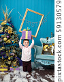 Happy little smiling boy holds christmas gift box. 59130579