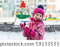 Cute adorable caucasian little girl winter portrait holding snowball in hands ready for snow fight 59133533