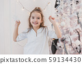 Small brunette girl is decorating a Christmas tree with silver snowflakes at home. 59134430