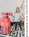 Lovely little girl playing with Christmas giftboxes, building a pyramid. 59134472