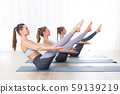 Group of young sporty attractive women in yoga studio, practicing yoga lesson with instructor 59139219