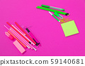 Two groups of pink and bright green office equipment are lying on opposite sides on pink surface 59140681