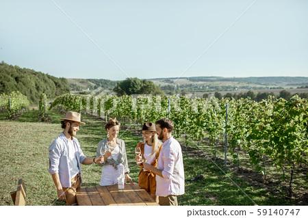 Friends tasting wine on the vineyard 59140747