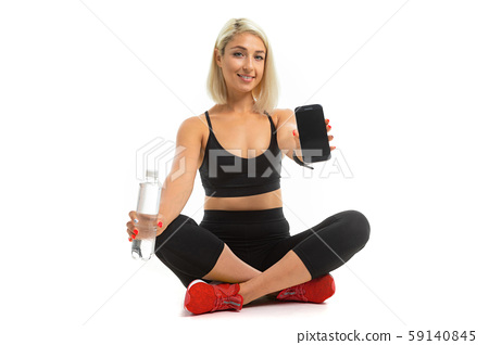 Beauiful sport caucasian girl sits on floor in res sneakers, cross legs, shows a mobile phone and 59140845