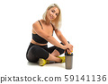 Sport caucasian girl sits on a floor in sport wear and keep a bottle with water in her hands 59141136