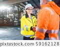 worker and customer in warehouse doing Handshake 59162128