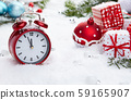 Red vintage alarm clock in the snow 59165907