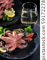 Stuffed octopus in white wine with lemon cooked in the oven on a black background. Atmospheric wonderful rich romantic dinner with sparkling white wine 59172278