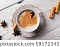 Beautiful cup of traditional indian masala chai tea on with star anise and cinnamon on a shabby wooden texture background. 59172343
