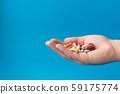 A handful of colored pills on the palm. Medical 59175774