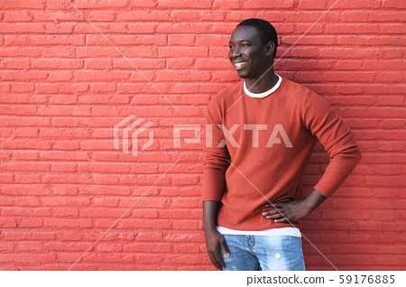 African Young Man Smiling And Leaning On Red Wall 59176885