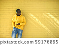 African Young Man Listening Music Leaning On Yellow Wall 59176895
