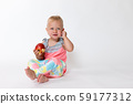 Whole figure of smilling toddler girl sitting and 59177312
