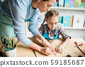 Young teacher helping cute girl with handmade decorations for holiday at lesson 59185687