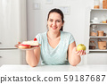 Making Right Choice. Chubby girl sitting at kitchen choosing between plate with desserts and apple 59187687