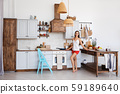 Lifestyle photo of cute girl standing by the stove 59189640