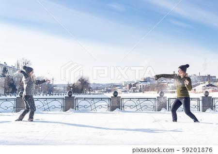 two women play snowballs 59201876