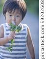 Boy holding a white clover 59202608