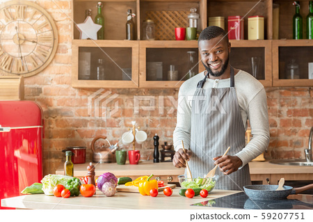 Smiling black man preparing fresh healthy salad at kitchen 59207751