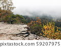 Beautiful autumn misty landscape, scenic view. Fog above forest valley. Rocky hills, pine and birch 59207975