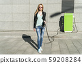 woman at the car charging station 59208284