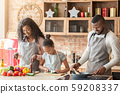 Cute afro girl helping parents at kitchen 59208337