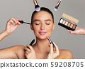 Beautiful woman and professional makeup artists with brushes 59208705