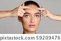 Problem skin. Girl crushing acne on her forehead 59209476
