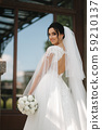 Gorgeous bride in elegant wedding dress with bouquet of white flowers in her wedding day 59210137