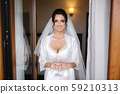 Portrait of gorgeous bride with glass of champagne at hotel in morning. Charming woman with great 59210313