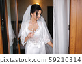 Portrait of gorgeous bride with glass of champagne at hotel in morning. Charming woman with great 59210314
