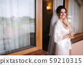 Portrait of gorgeous bride with glass of champagne at hotel in morning. Charming woman with great 59210315