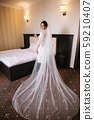 Morning of beautiful bride. Woman in white negligee in hotel. Back view 59210407
