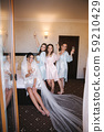 Gorgeous bride with best bridesmaids drinking champagne in hotel. Morning of bride. Sexy bridesmaids 59210429