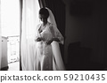 Morning of beautiful bride. Woman in white negligee in hotel 59210435