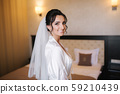 Morning of beautiful bride. Woman in white negligee in hotel 59210439