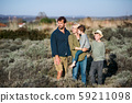 Young family with two small children standing outdoors in nature. 59211098
