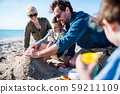 Young family with two small children sitting outdoors on beach, playing. 59211109