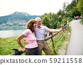 Senior pensioner couple hikers standing in nature, taking selfie. 59211558