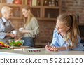 Little girl painting at kitchen while helping mom and granny 59212160