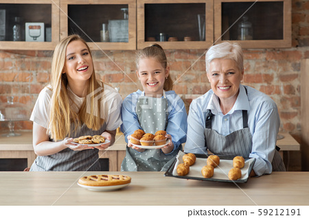 Cheerful women showing freshly baked home pastry 59212191